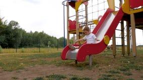 Um rapaz pequeno está jogando no campo de jogos das crianças A criança rola lentamente para baixo de um monte alto em um dia de v filme