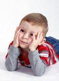 Um rapaz pequeno está pensando sobre? Foto de Stock