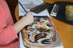 Um rapaz pequeno está pintando ao estilo da arte abstrato Imagem de Stock