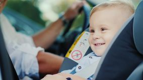 Um rapaz pequeno está sentando-se em um banco de carro perto de seu pai, sorrindo felizmente Conceito - segurança e cuidado vídeos de arquivo
