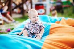 Um rapaz pequeno está sentando-se em um saco de feijão fotografia de stock