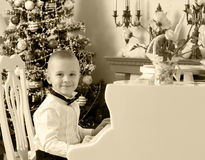 Um rapaz pequeno está sentando-se no piano foto de stock royalty free