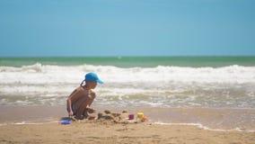 Um rapaz pequeno est? jogando na areia no mar, os p?s e os dedos pequenos, um fundo da areia amarela do mar e ?gua azul