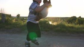 Um rapaz pequeno guarda um carneiro macio do brinquedo que corre felizmente com ela no movimento lento filme