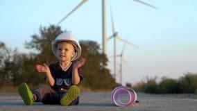 Um rapaz pequeno joga com capacete do construtor Põe-no sobre e aplaude-o alegremente as mãos video estoque