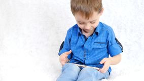 Um rapaz pequeno joga um jogo educacional através do Internet A criança olha a tela do smartphone e dos risos video estoque