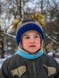 Um rapaz pequeno joga no campo de jogos Fotos de Stock