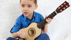 Um rapaz pequeno joga uma guitarra acústica das crianças e canta uma música Música, a educação das crianças O conceito de um feli vídeos de arquivo
