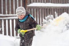 Um rapaz pequeno limpa trajetos de uma p? na jarda da neve fotografia de stock