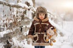 Um rapaz pequeno na pele, jogando no inverno fora Floresta nevado fotografia de stock