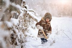 Um rapaz pequeno na pele, jogando no inverno fora Floresta nevado foto de stock royalty free