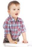 Um rapaz pequeno na tabela desenha Fotos de Stock Royalty Free
