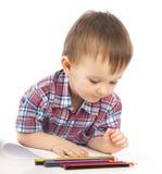 Um rapaz pequeno na tabela desenha Imagem de Stock