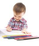 Um rapaz pequeno na tabela desenha Fotografia de Stock