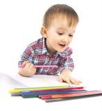 Um rapaz pequeno na tabela desenha Imagens de Stock Royalty Free