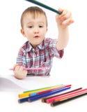 Um rapaz pequeno na tabela desenha Fotografia de Stock Royalty Free
