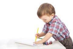 Um rapaz pequeno na tabela desenha lápis coloridos Foto de Stock Royalty Free