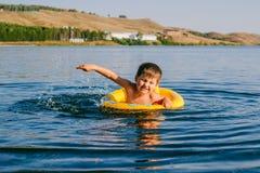 Um rapaz pequeno nada no boia salva-vidas no lago imagem de stock royalty free