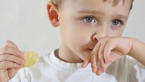 Um rapaz pequeno no movimento lento que come microplaquetas de batata, close-up filme