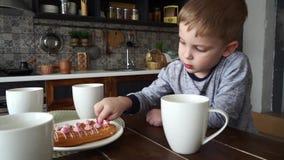 Um rapaz pequeno pensativo senta-se em uma tabela com um chá e os bolos do circley Lambendo seu dedo Retrato filme