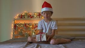 Um rapaz pequeno que abre um presente de um calendário do advento que esteja pendurando em uma cama que seja iluminada com luzes  video estoque