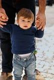 Um rapaz pequeno que aprende andar da m?o de um adulto imagem de stock