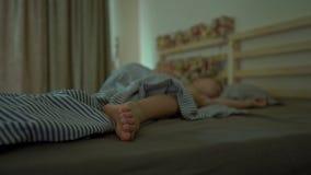 Um rapaz pequeno que dorme em sua cama com um calendário do advento para iluminar com luzes de Natal brilha em uma parte traseira vídeos de arquivo