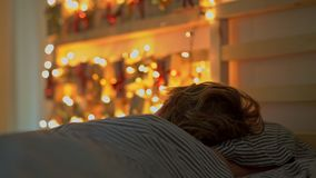 Um rapaz pequeno que dorme em sua cama com um calendário do advento para iluminar com luzes de Natal brilha em uma parte traseira video estoque