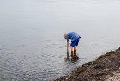 Um rapaz pequeno que está andando na água Imagens de Stock Royalty Free