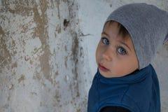 Um rapaz pequeno que está no canto ofendido fotografia de stock