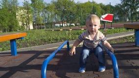 Um rapaz pequeno que faz esportes no campo de jogos Fotografia de Stock