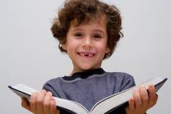 Um rapaz pequeno que lê um livro grande imagens de stock royalty free