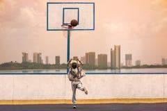 Um rapaz pequeno que salta e que faz o objetivo que joga o streetball, basquetebol O basquetebol de jogo oposto aos arranha-céus  Fotos de Stock