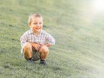 Um rapaz pequeno que senta-se em uma inclinação verde imagens de stock