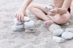 Um rapaz pequeno que senta-se na areia que faz a torre das pedras Fotos de Stock