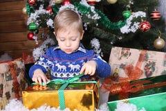 Um rapaz pequeno que senta-se sob a árvore de Natal Imagens de Stock