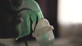 Um rapaz pequeno respira através da máscara transparente do inalador A criança respira no inalador Máscara da inalação na cara o vídeos de arquivo