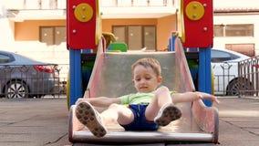 Um rapaz pequeno rola para baixo uma corrediça no campo de jogos no dia ensolarado do verão Recreação e jogos para crianças no ar video estoque