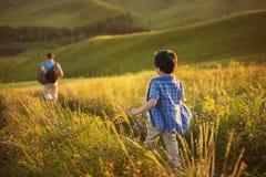 Um rapaz pequeno segue seu pai em um campo Foto de Stock Royalty Free