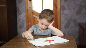 Um rapaz pequeno senta-se na tabela e nas emoções das mostras, não querendo tirar com lápis Crianças prées-escolar da educação filme