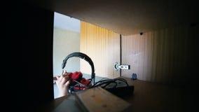 Um rapaz pequeno toma os fones de ouvido da prateleira - interior velho do russo filme