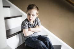 Um rapaz pequeno triste que senta-se nas escadas na casa no tempo do dia foto de stock royalty free