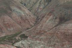 Um rebanho dos carneiros que pastam perto do pé da montanha coberta com a vegetação e as listras vermelhas foto de stock