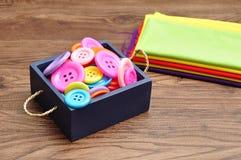 Um recipiente azul encheu-se com os botões e uma pilha de material colorido Fotografia de Stock Royalty Free