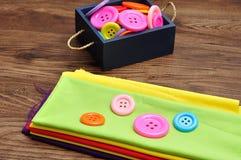 Um recipiente azul encheu-se com os botões e uma pilha de material colorido Foto de Stock Royalty Free