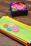 Um recipiente azul encheu-se com os botões e uma pilha de material colorido Fotos de Stock Royalty Free