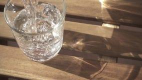 Um redemoinho da água em um vidro em um movimento lento da tabela vídeos de arquivo