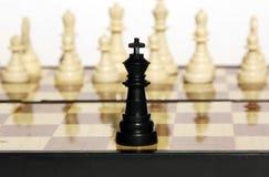 Um rei preto de encontro a um número de figuras brancas Imagem de Stock