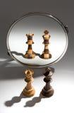 Um rei preto e uma rainha branca estão olhando em um espelho para ver-se como um par colorido preto e branco Imagem de Stock Royalty Free
