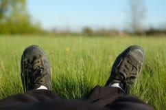 Um relaxamento da pessoa alongado em um prado Imagens de Stock